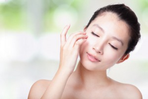 close up of woman relax touch her closed eyes and face with smile, concept for eyes care or skin care, with nature green background, model is a asian girl